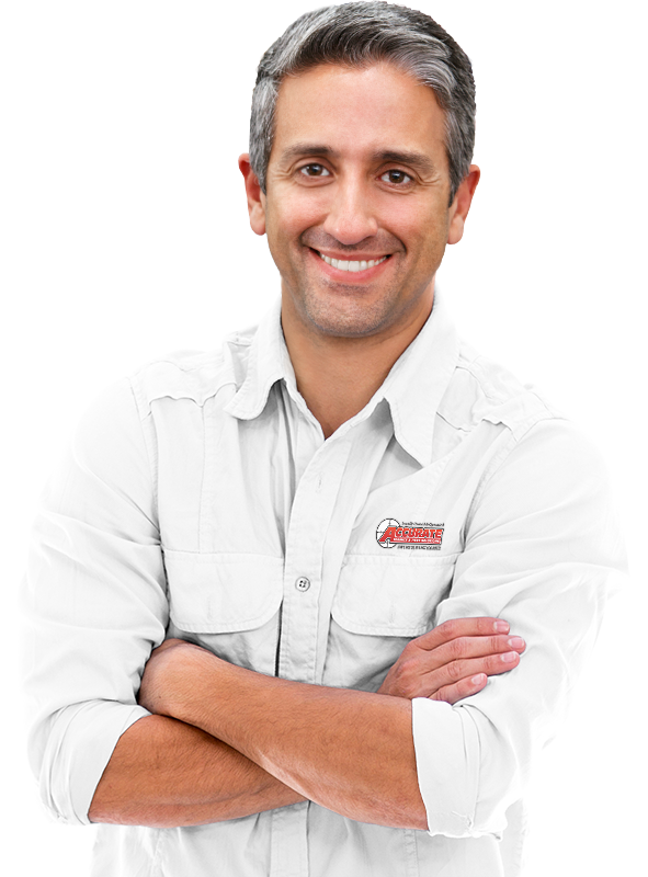 an accurate pest services technician smiling with his arms crossed wearing a white shirt