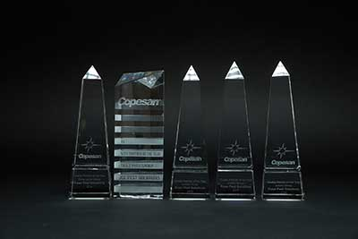 5 consecutive copesan award trophies on black background