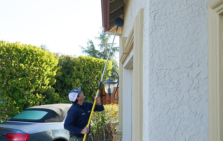 a pest control service technician performing dewebbing services on the exterior of a home