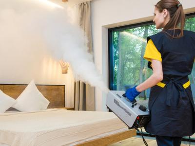 A technician treats a room for bed bugs with steam