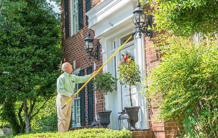 nashville pest control technician performing cobweb removal