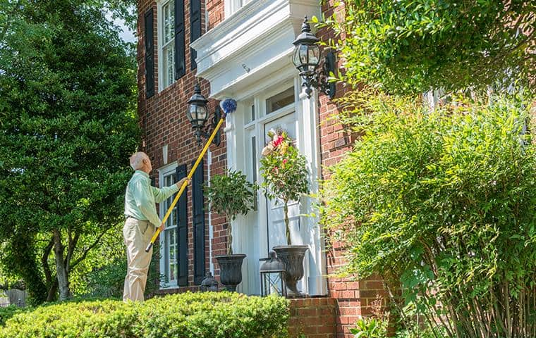 brentwood pest control technician removing spider webs