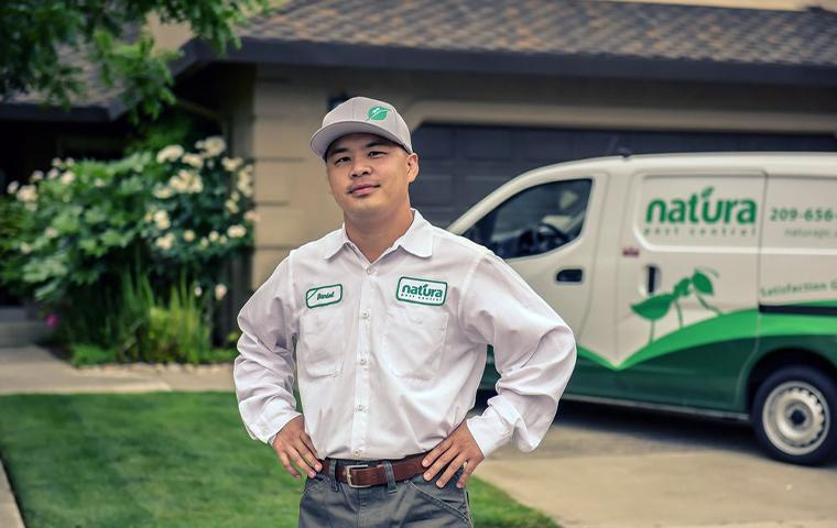 a natura pest control technician in front of van